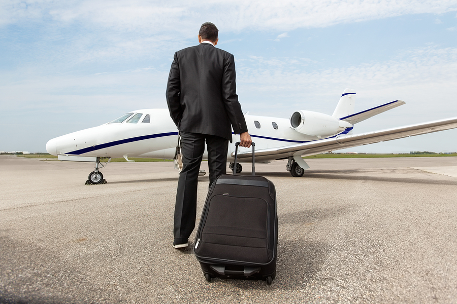 Rear view of businessman with luggage walking towards corporate
